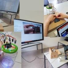 Junger Mann sitzt vor dem PC. Neben ihm steht ein leeres Gurkenglas, das mit vielen Steckern vernetzt ist.